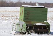 Snowy owl perching on portable farm grain feeder.  Winter in Minnesota poster