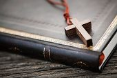 Closeup of simple wooden Christian cross necklace on holy Bible poster