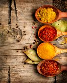 Spices. Spice over Wood. Herbs. Curry, Saffron, turmeric, cinnamon and other over wooden background poster