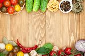 Fresh ingredients for cooking: pasta, tomato, cucumber, mushroom and spices over wooden table background with copy space poster