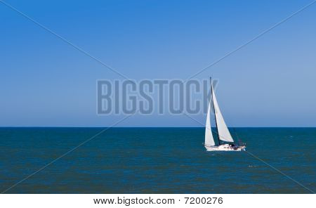Sailboat At Sea Against Clear, Blue Sky.