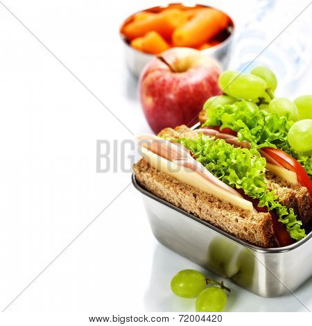 Lunch box with sandwich, fruits and water on white background