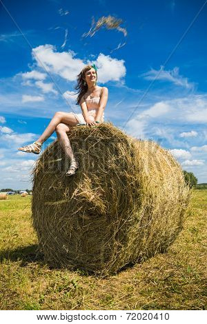 Young woman sit on a newly built hay stack.