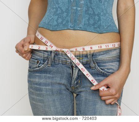 Woman In Jeans Measuring Waist