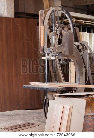Old bandsaw cutting wood in wrorkshop