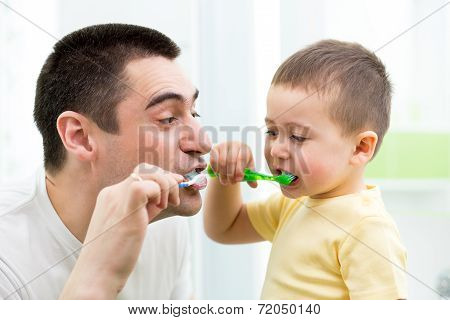 Child Boy And His Dad Brushing Teeth In Bathroom