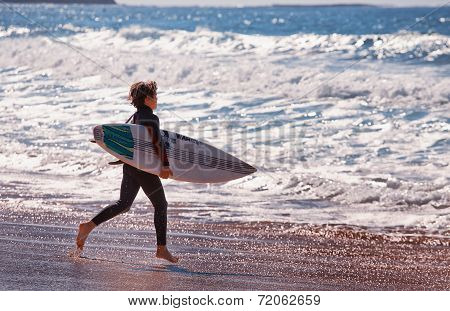 Australian boy running towards the surf