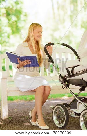 family, child, leisure, education and parenthood concept - happy mother with baby stroller reading book in park