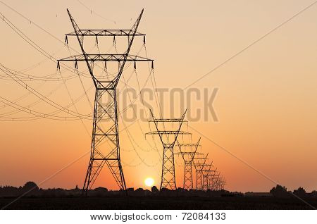Row of high voltage pylons in an orange sunset