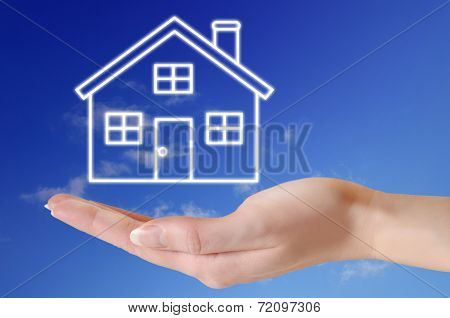 House in hand over blue sky concept