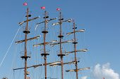 Masts and sails of huge sailing boat against the background of blue sky poster