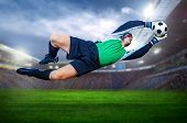 Football goalkeeper in action on field of stadium poster