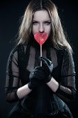 Pretty gothic girl in black dress with lollipop over black poster