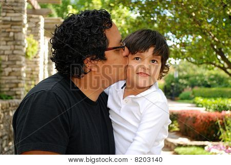 Hispanic father kissing his adorable son
