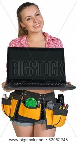 Woman in tool belt showing opened laptop with blank screen