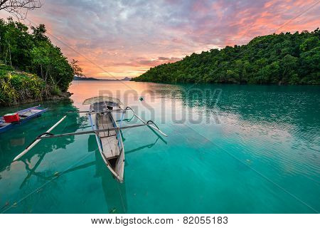 Breathtaking colorful sunset and traditional boat floating on scenic blue lagoon in the Togean (or Togian) Islands Central Sulawesi Indonesia upgrowing travel destination. poster