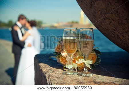 Two Glasses With Champagne And A Bouquet Of Roses On A Background Of Loving Couples