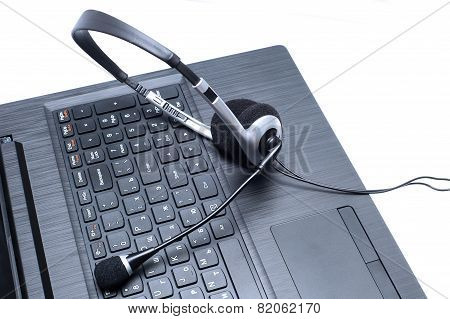 Headset lying on a laptop computer keyboard conceptual of online communication or a call centre poster