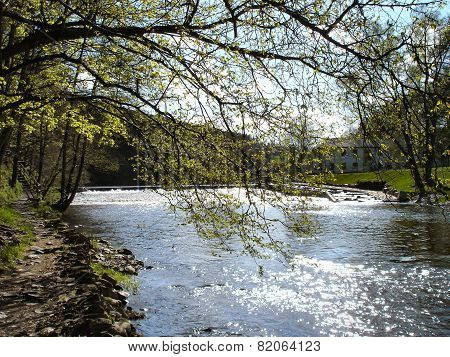 Hiking path at the Zschopau River in Saxony, Germany; landscape in the spring; meadows, deciduous trees und blue sky with white clouds poster