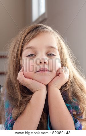 Little girl with hands up her chin