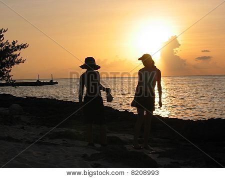 kids silhouetted in the sunset on the beach