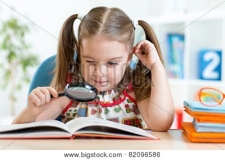 funny child reads book using magnifier sitting at table