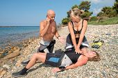 Scuba Divers performing CPR training on a casualty on a beach poster