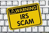 IRS Scam Warning Sign A yellow sign with the words IRS Scam on a keyboard poster