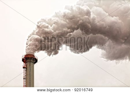 Closeup of dirty dark smoke clouds from a high industrial chimney