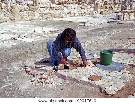 Archaologist restoring floor, Cyprus.