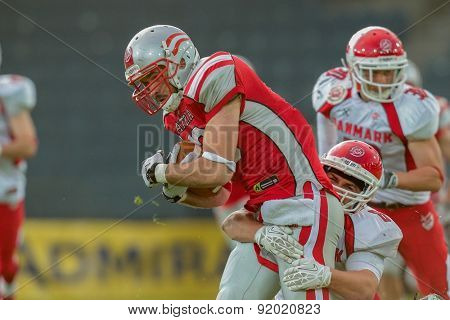 GRAZ, AUSTRIA - MAY 31, 2014: WR Thomas Haider (#13 Austria) is tackled by LB Mikkel Vangsgard (#8 Denmark).