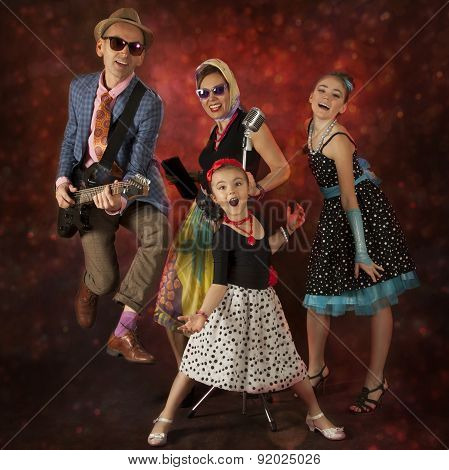 Rock musician family have fun playing music and singing on a black background with glowing lights poster