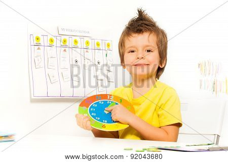 Smiling boy holding colorful carton clock sitting