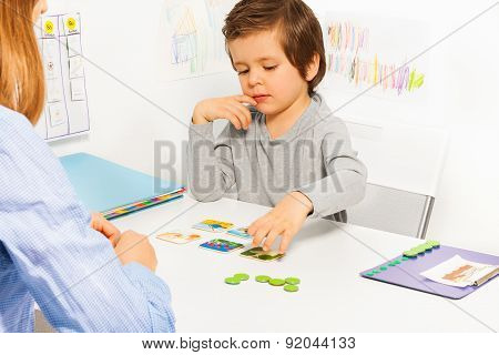 Preschooler boy and developing game with card