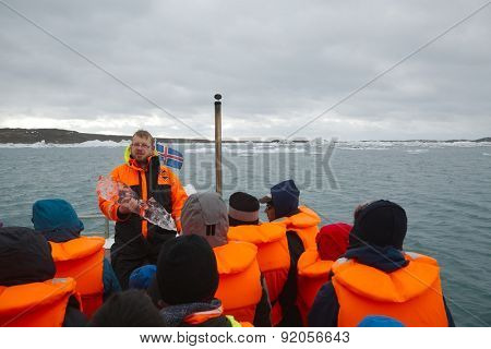 JOKULSARLON, ICELND - MAY 10, 2015: Tour guide talking about the the icebergs on an amphibian tour on the glacier lake Jokulsarlon, Iceland