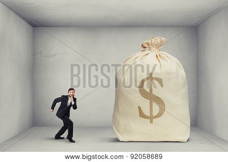 businessman in formal wear showing silent sign and walking on tiptoe to the big bag of money in grey room
