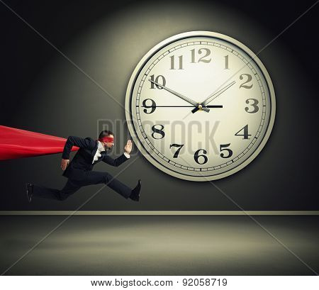 serious businessman wearing like superman running against big white clock in dark room