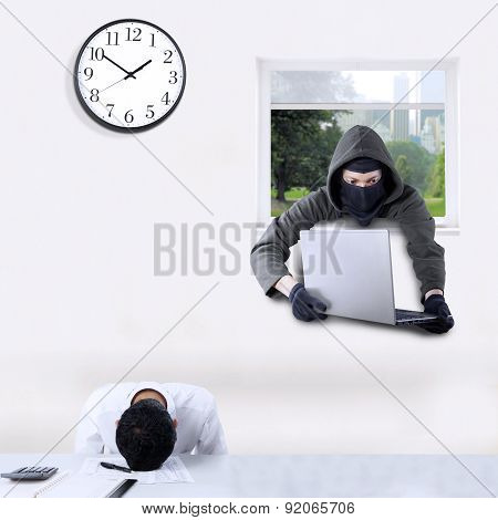 Thief Stealing Laptop In Office
