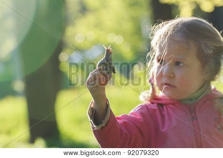 Curious Two Years Old Preschooler Girl With Short Pigtails Is Holding Edible Snail