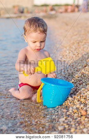 Cute Baby Boy Playing On The Beach