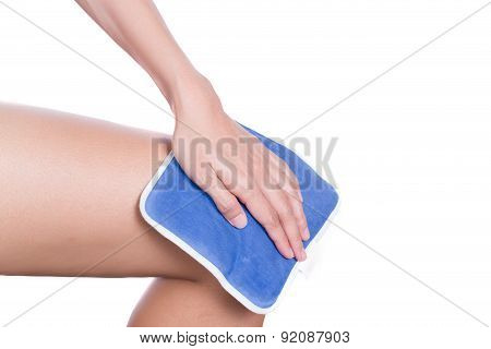 A Woman Applying Cold Pack On Swollen Hurting Knee
