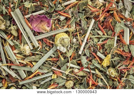 digestion and bloating herbal tea  with peppermint, spearmint, honeybush, hibiscus. osmanthus, chamomile. lemon grass, saffron, ginger, lemon balm - closeup background