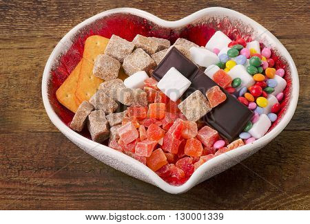 Different Kind Of Sugar, Candies And Cookies In Heart Shaped Bowl.