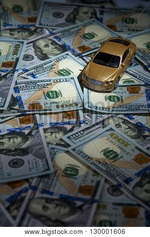 Golden toy car on the heap of one hundred dollar bills