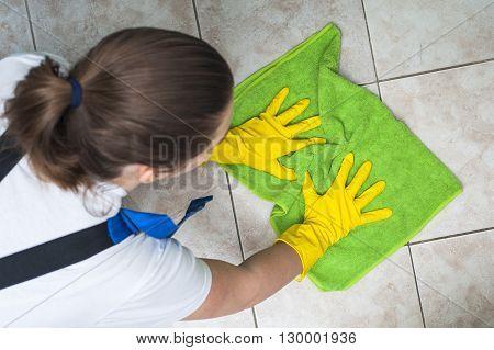 Female janitor in work wear washing floors.