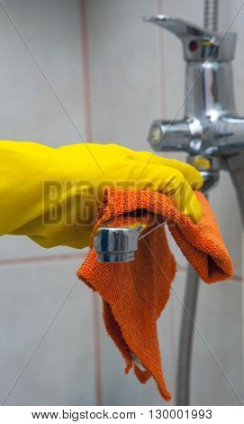 Closeup of woman's hand with yellow glove wiping faucet. Cleaning concept.