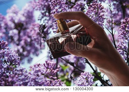 Girl holding stylish bottle of Perfume over flowers background