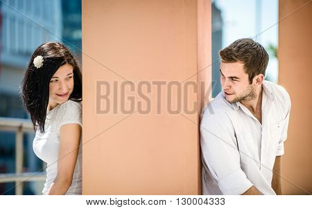 Two people sitting on opposite side of big collumn - outdoor in street