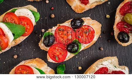 Italian bruschetta with cherry tomatoes, herbs, olives, mozzarella on toasted crusty ciabatta bread
