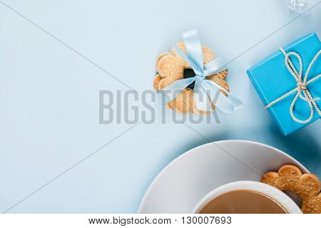 Coffee and cookies on blue background from the top